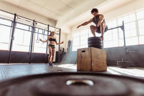 Pareja durante sesión de entrenamiento intenso en gimnasio - foto de stock