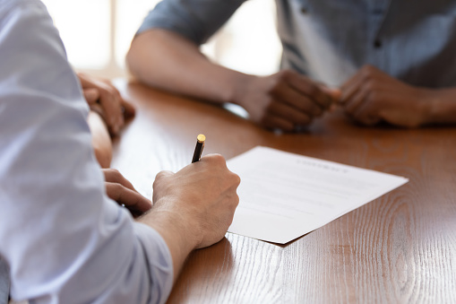 843533912 istock photo Couple during meeting with realtor signing rental agreement closeup image 1262889135