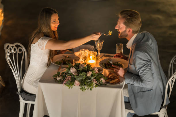 couple during romantic dinner woman feeding man with fork on romantic candlelight dinner. Top perspective honeymoon, vacation romance table for two stock pictures, royalty-free photos & images