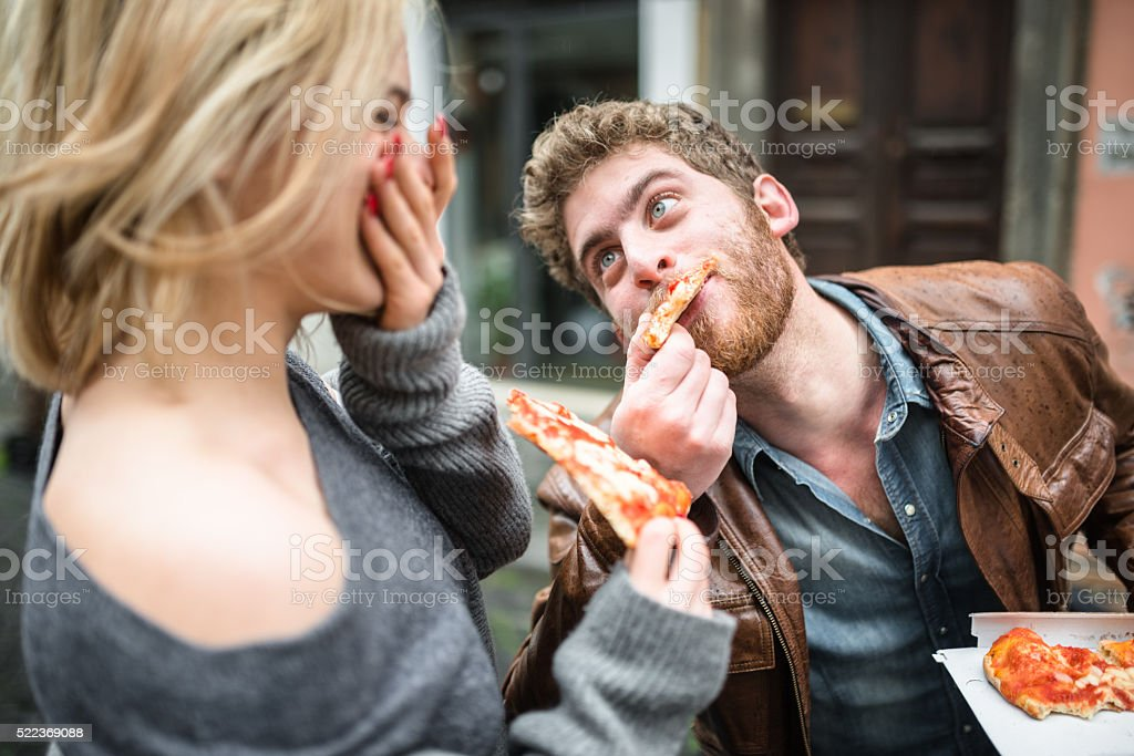 couple eating a pizza in italy stock photo