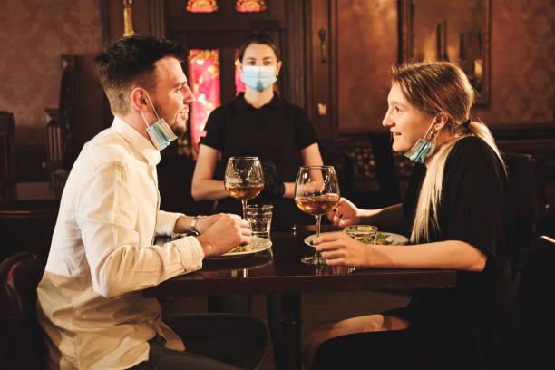 Couple eating at bar reopening after quarantine restriction stock photo
