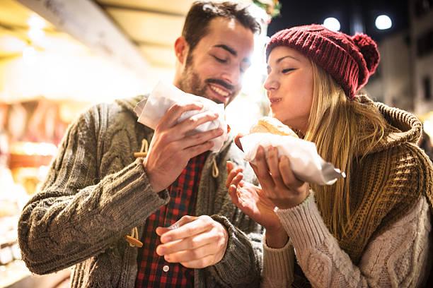 paar essen auf dem weihnachtsmarkt - italienischer weihnachten stock-fotos und bilder