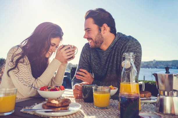 Couple eating breakfast outdoors. stock photo