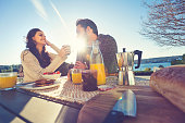 Couple eating breakfast outdoors.
