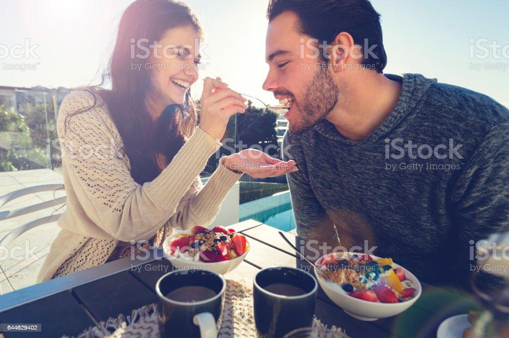 Couple eating breakfast outdoors. stock photo