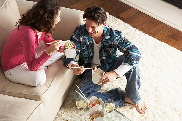 Couple eating Chinese food in living room  chinese takeout stock pictures, royalty-free photos & images
