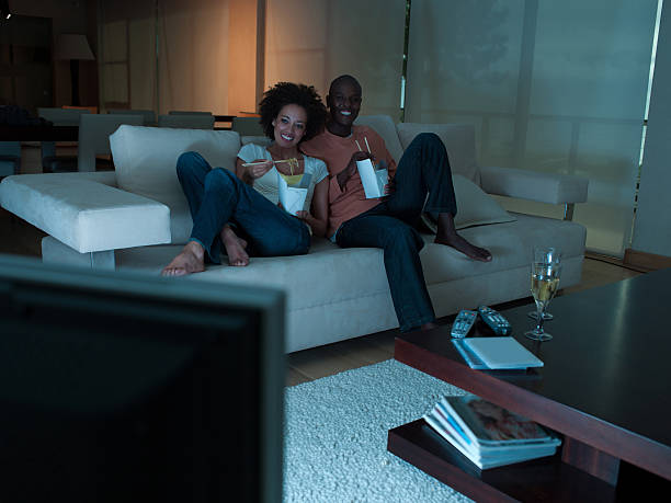 A couple eating Chinese food watching television stock photo