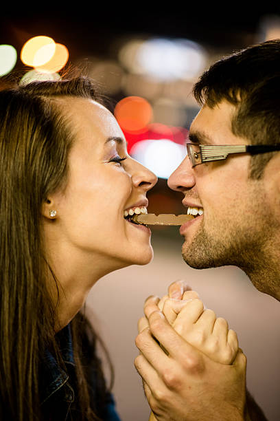 Couple eating chocolate on date stock photo