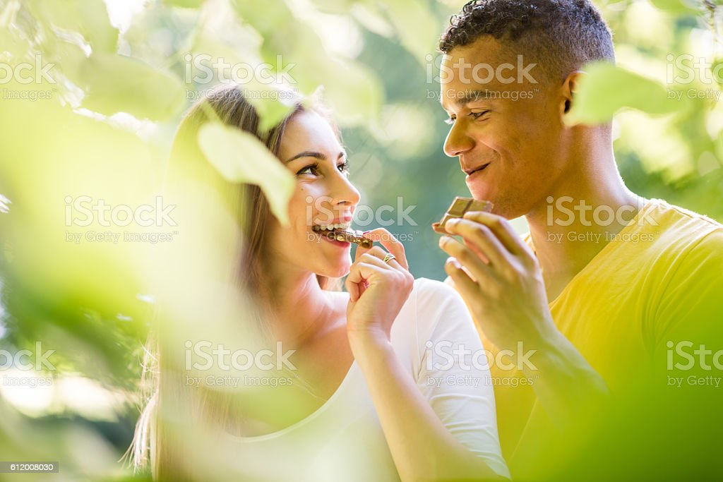 Couple eating chocolate together stock photo