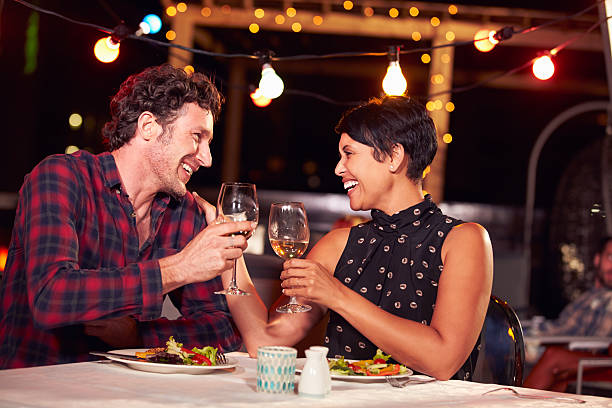 Couple eating dinner at rooftop restuarant Couple eating dinner at rooftop restuarant date night romance stock pictures, royalty-free photos & images