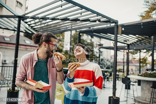 Young couple is eating hot dogs outdoors