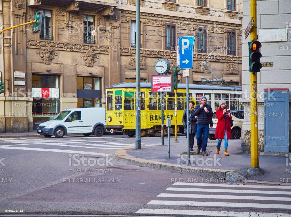 A couple eating Ice cream in front of a tram crossing a street of Zona Magenta neighborhood. Milan, Italy. stock photo