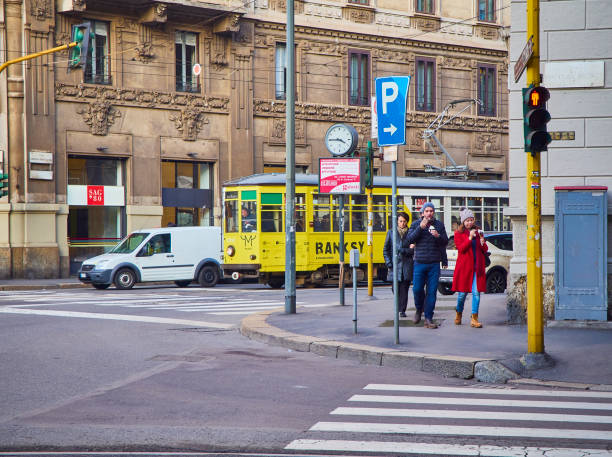A couple eating Ice cream in front of a tram crossing a street of Zona Magenta neighborhood. Milan, Italy. - foto stock