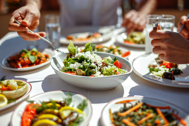 couple  eating lunch with fresh salad and appetizers - vegetariano foto e immagini stock