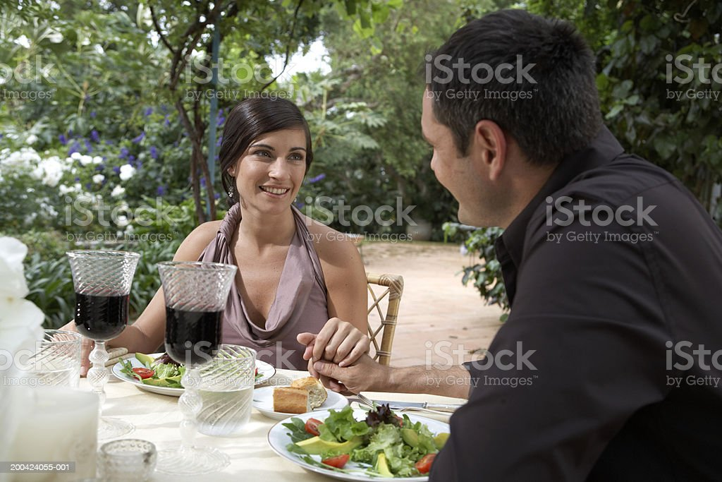 Couple eating outdoors, holding hands at table, side view of man royalty-free stock photo