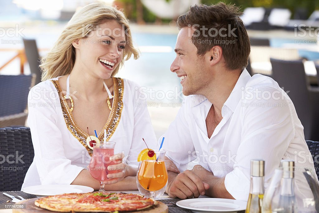 Couple eating pizza and drinking tropical drinks outside royalty-free stock photo