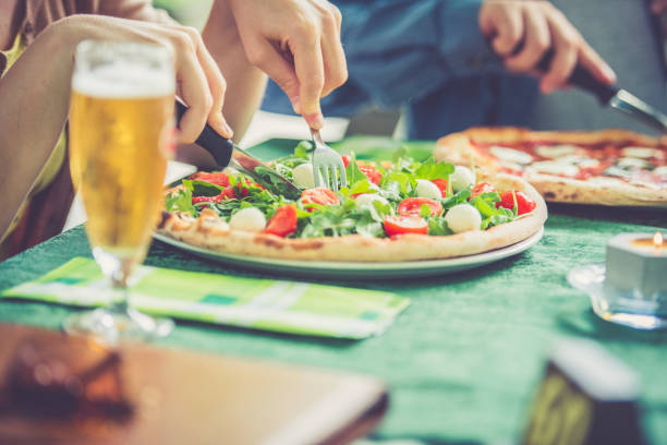 couple eating pizza outdoors close up - pizzeria stock photos and pictures