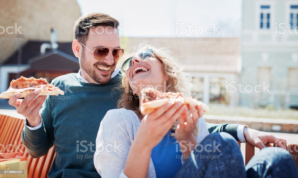 Couple eating pizza outdoors. Dating, consumerism, food, lifestyle concept stock photo