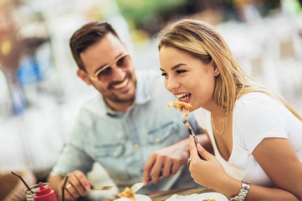 pareja comiendo pizza snack al aire libre. están compartiendo pizza y comiendo. - couple lunch outdoors fotografías e imágenes de stock
