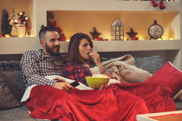 paar essen pop hühneraugen während des fernsehens - mädchen night snacks stock-fotos und bilder