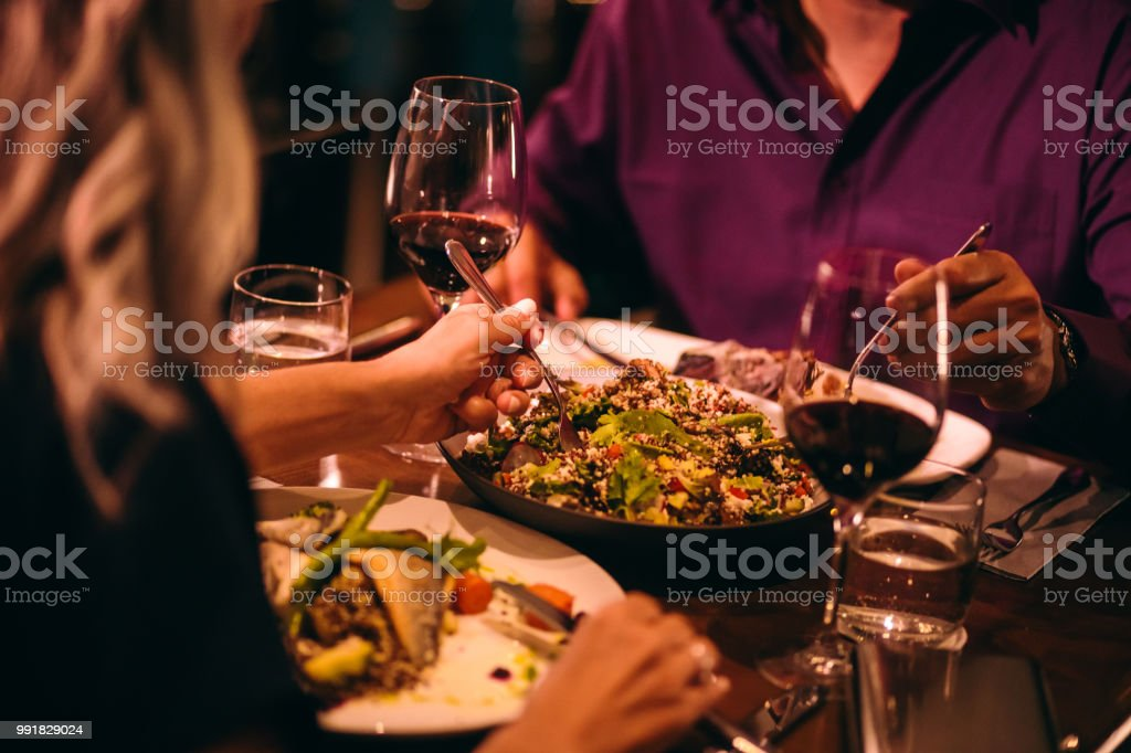 Couple eating quinoa salad and healthy dinner at restaurant stock photo