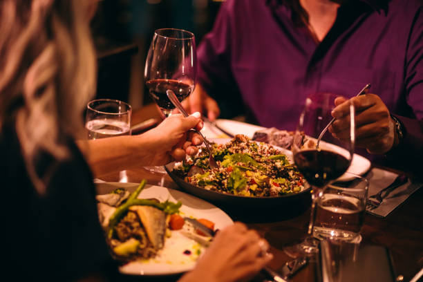 Couple eating quinoa salad and healthy dinner at restaurant Couple on dinner date night eating healthy food with quinoa salad and drinking red wine romantic activity stock pictures, royalty-free photos & images