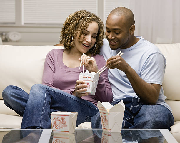 Couple eating take-out Chinese food stock photo