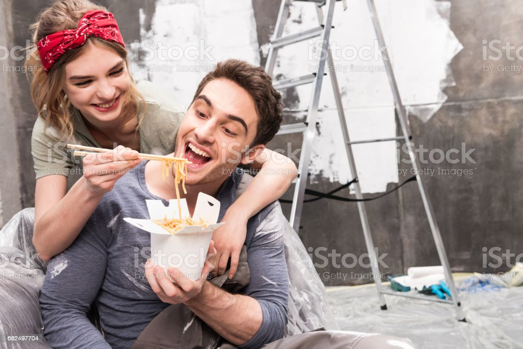 couple eating thai food while resting during renovation home process royalty-free stock photo