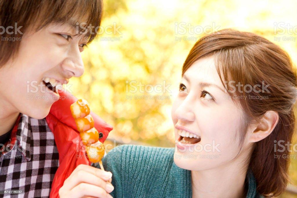 Couple eats the Mitarashi dango royalty-free stock photo