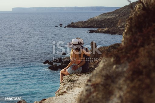 Couple embrace and sitting on the coastline, beautiful view to sea