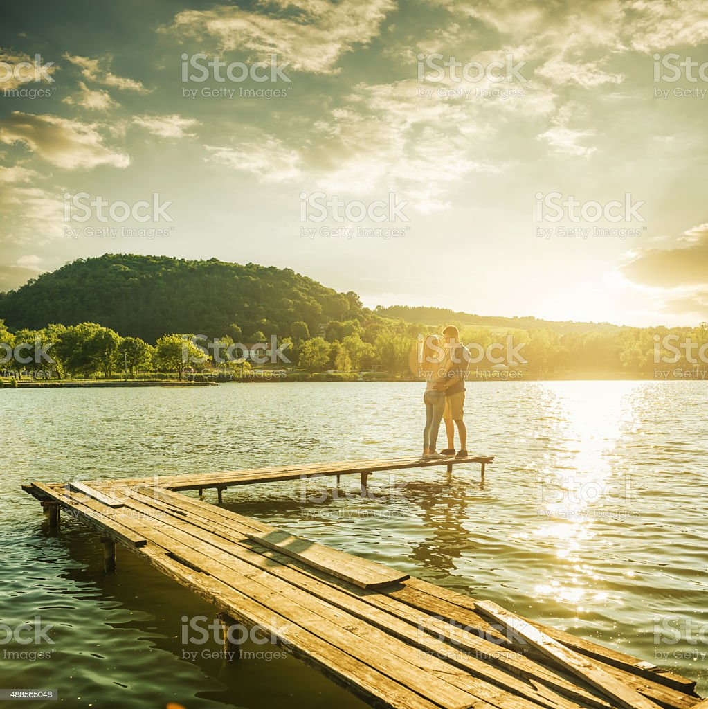 Couple embrace on the pier stock photo