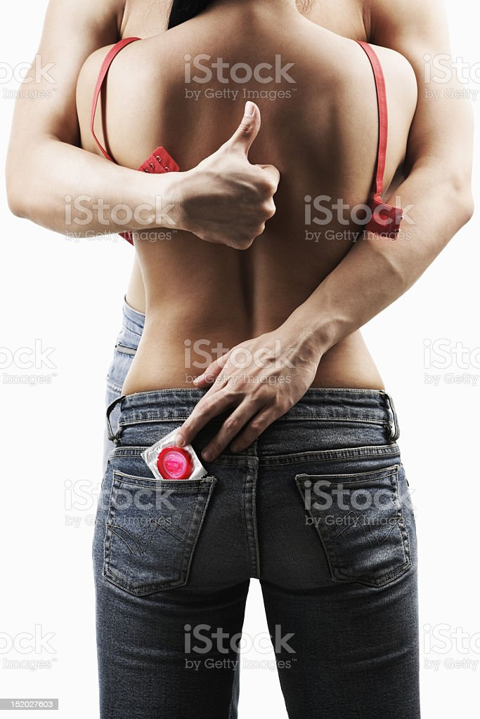 A couple embraces as a man gives thumbs up and holds condom stock photo