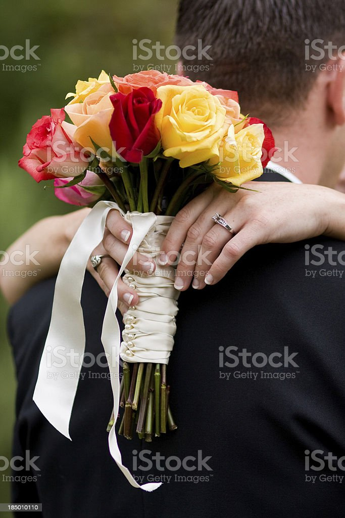 Couple embracing & bride holding a bouquet of roses, wedding royalty-free stock photo