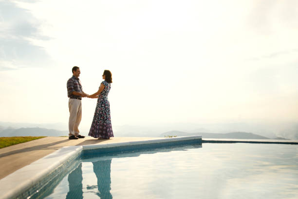 couple embracing and looking at each other, outdoors in the nature, near a swimming pool - vicino foto e immagini stock