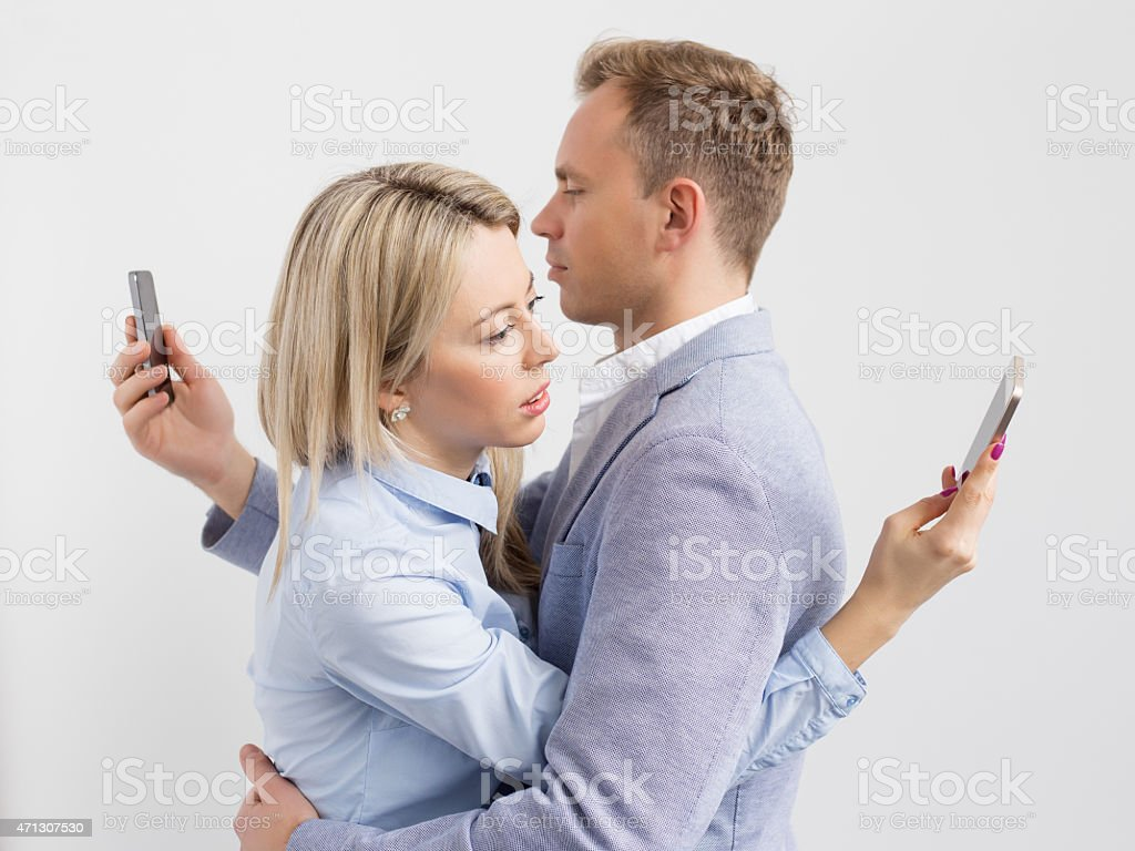 Couple embracing and still using their mobile phones stock photo