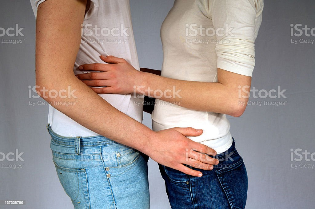 A couple embracing by their waists stock photo