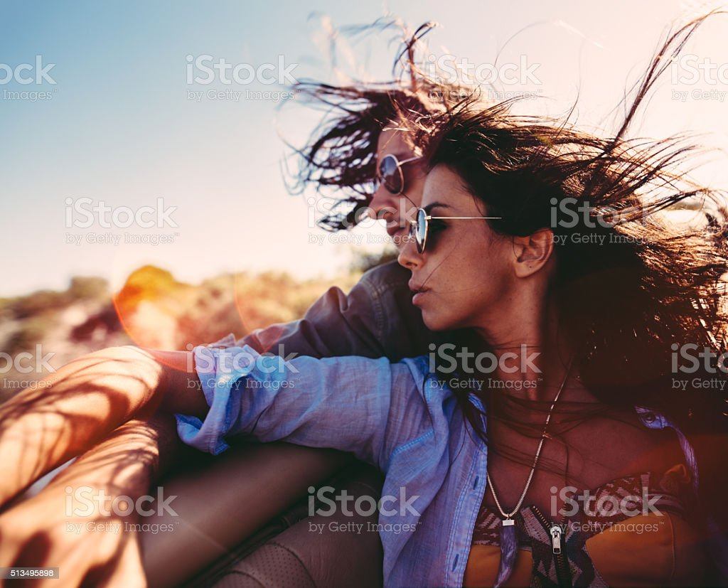 Couple embracing during road trip in back seat of convertible stock photo