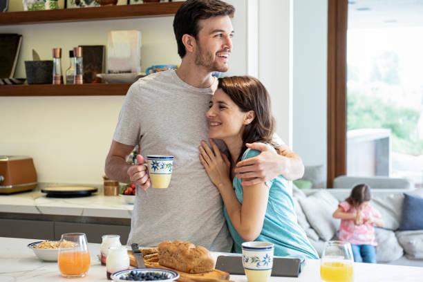 pareja abrazándose - happy couple sharing a cup of coffee fotografías e imágenes de stock