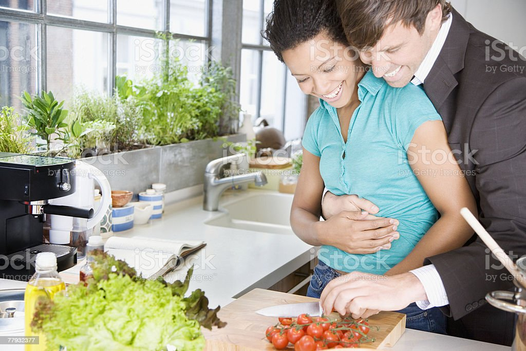 Couple embracing in a kitchen chopping cherry tomatoes royalty-free stock photo