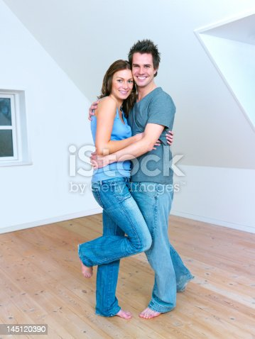 istock Couple embracing in a new house 145120390
