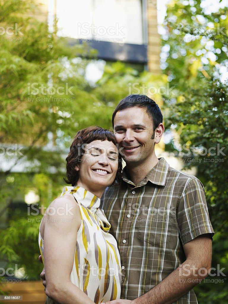 Couple embracing in backyard garden royalty free stockfoto