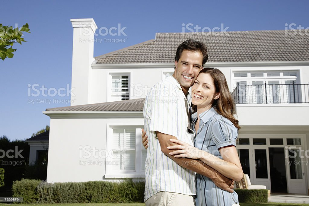 A couple embracing in front of a large home stock photo