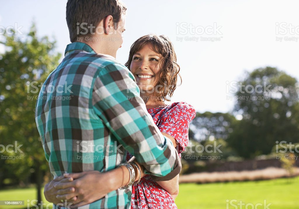 Couple embracing in park, smiling royalty-free stock photo