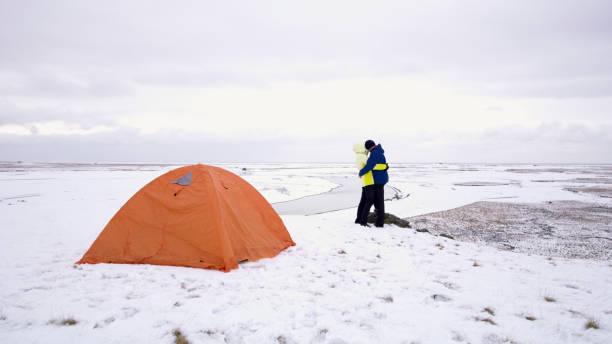 paar, umarmen, in der nähe von zelt im winter, island - zelt stehhöhe stock-fotos und bilder