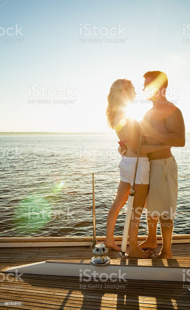 Couple embracing on sailboat at sunset royalty-free stock photo