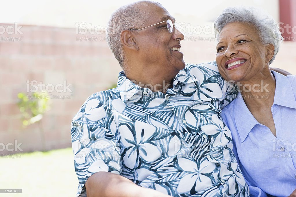 Couple embracing outdoors smiling stock photo