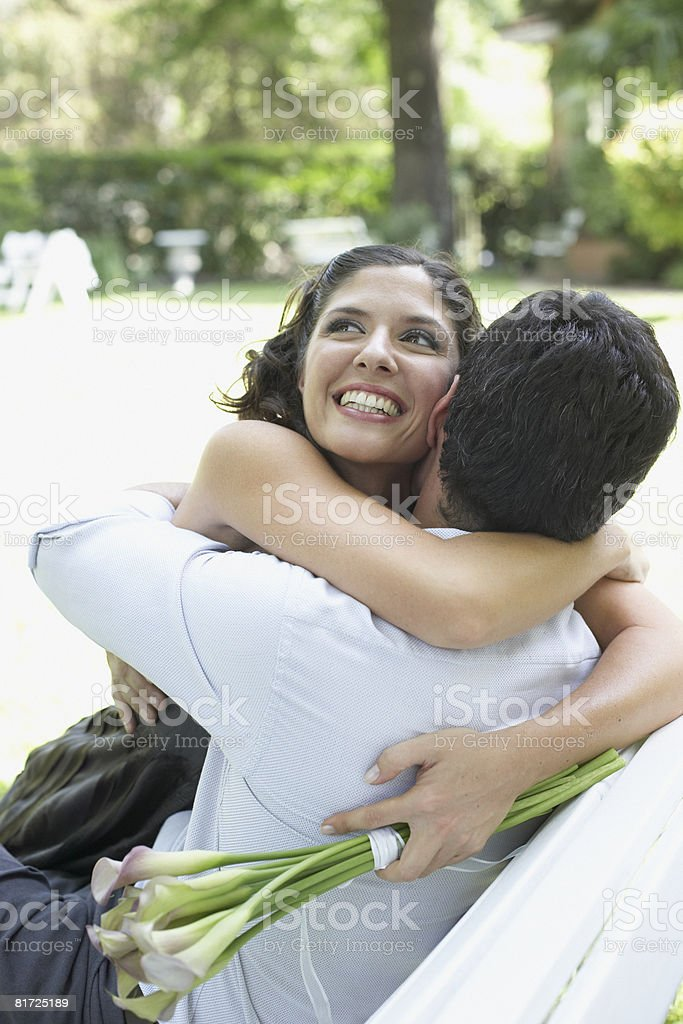Couple embracing outdoors with flowers smiling royalty-free stock photo