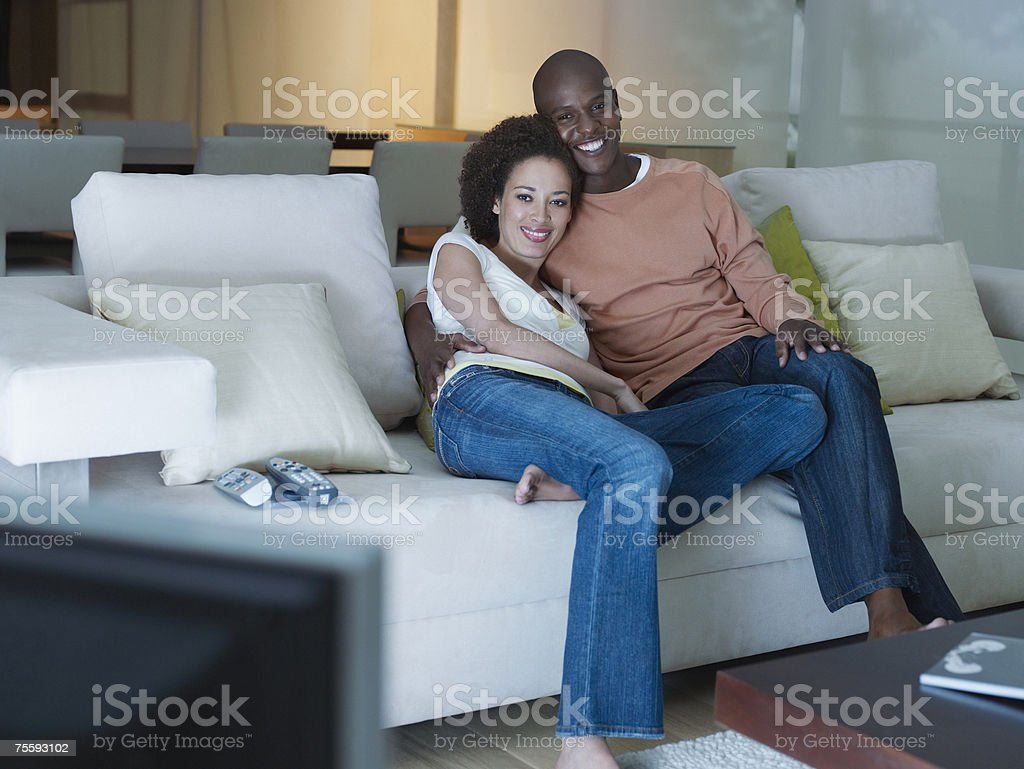 A couple embracing watching the television stock photo