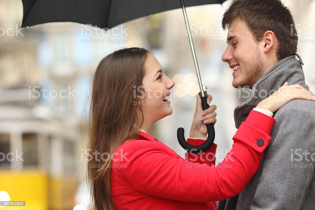 Couple encounter in the street under the rain stock photo