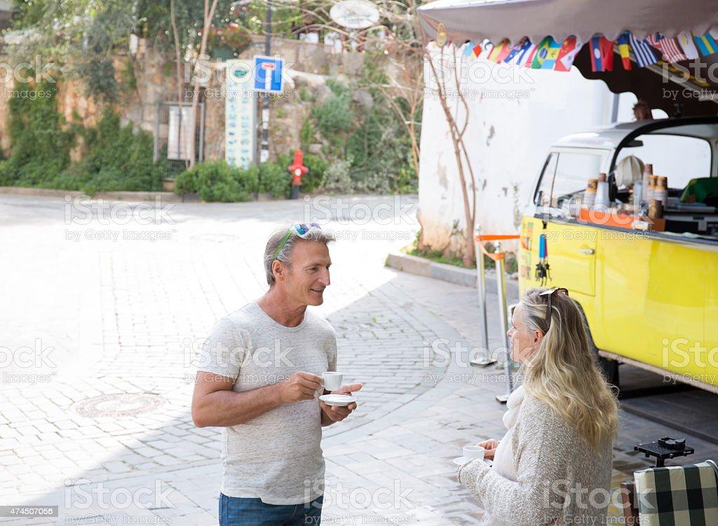 Couple enjoy coffee at streetside espresso stand stock photo
